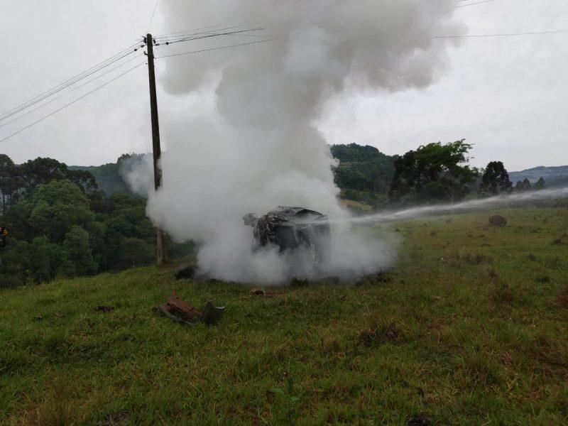 De acordo com o Corpo de Bombeiros Voluntários de Lindóia do Sul, a mulher estava sozinha no carro que saiu da rodovia e capotou em uma ribanceira. O veículo pegou fogo após o acidente. – Foto: Rádio Atual FM/ND