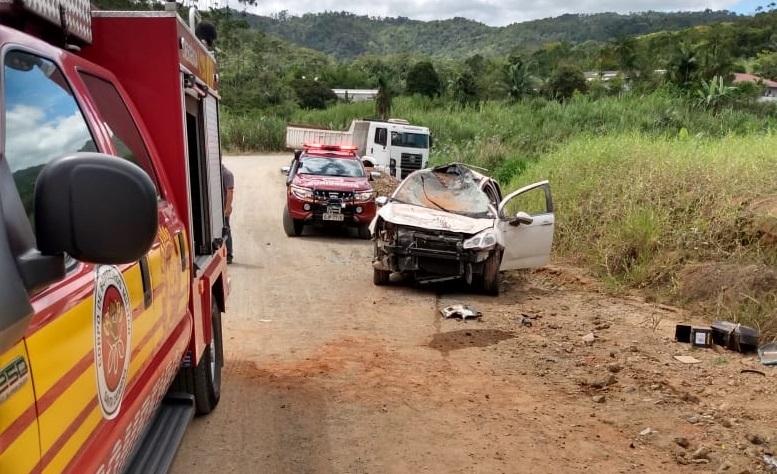 Foto do acidente mostra o carro com a frente destruída. Na imagem também aparecem as viaturas dos bombeiros. É uma rua de barro, com vegetação no entorno.