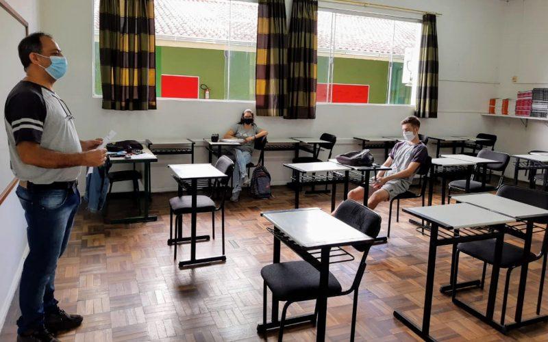 Imagem de uma sala de aula. Na frente do quadro aparece o professor usado máscara. Nas mesas estão dois alunos, um garot o e uma garota também de máscara e com distanciamento.