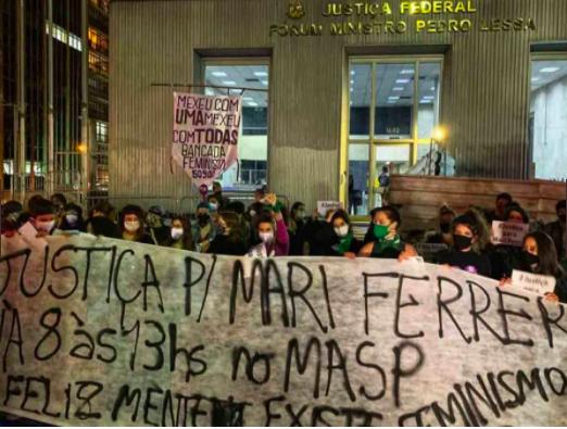 """Um faixa """"justiça p/ Mari Ferrer"""" com mulheres segurando"""