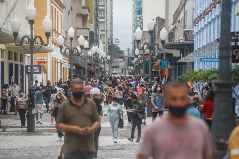 Centro de Florianópolis com movimento e possível ver pessoas usando máscaras