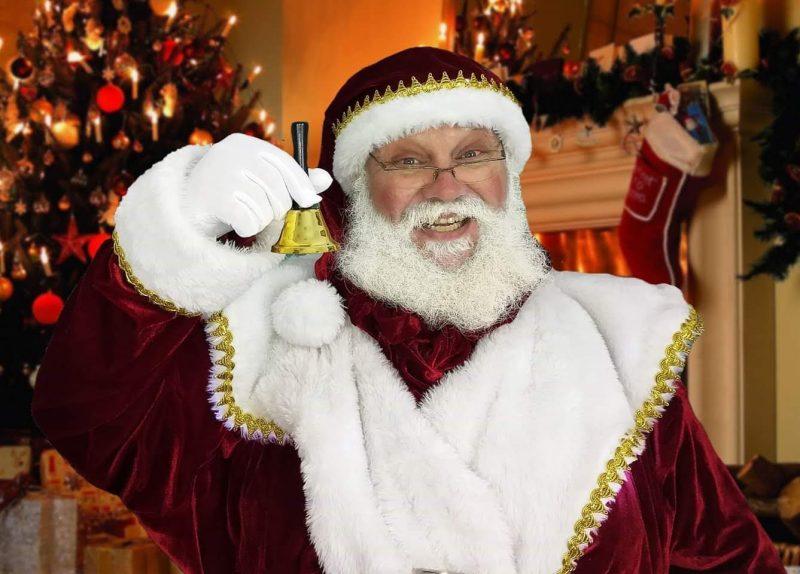 Papai Noel olha para a câmera e sorri. Ele segura um sino