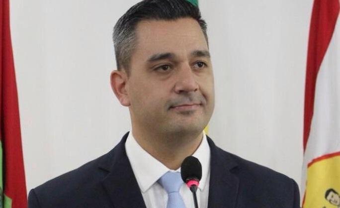 Fotografia de perfil do vereador reeleito Alexandre Matias. Ele veste terno e está usando um microfone.