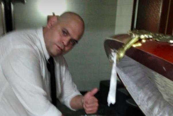 Funcionário posou para foto ao lado do caixão onde estava o corpo de Maradona – Foto: Reprodução