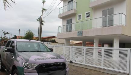 Um carro da Polícia Militar ao lado de um prédio