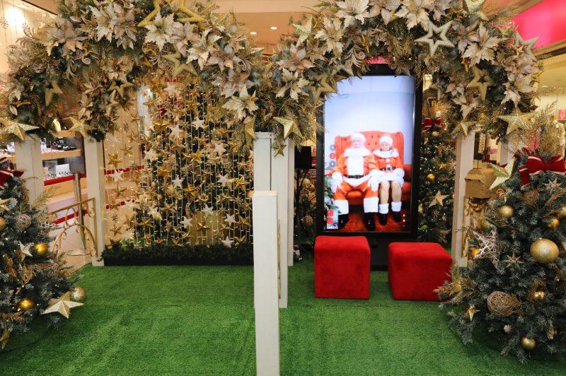 Totem virtual com Papai Noel e Mamãe Noel. Há decoração de natal