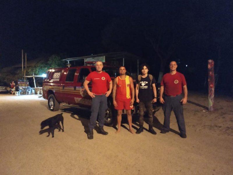 Guarnição do Grupamento de Busca e Salvamento e o jovem resgatado. Estão quatro homens em pé em frente ao carro dos bombeiros