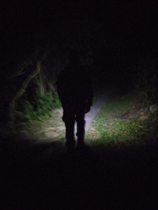 Trilha à noite. Aparece apenas a sombra de um homem iluminando o caminho