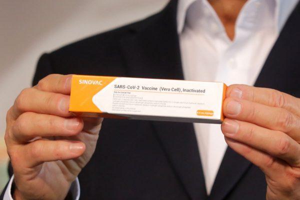 Vacina da coronavac em uma caixa laranja e branca