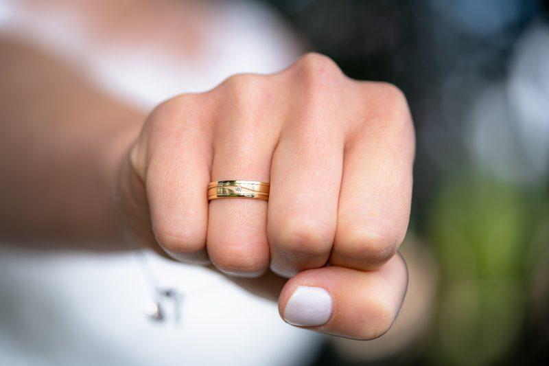 mão feminina com aliança de ouro