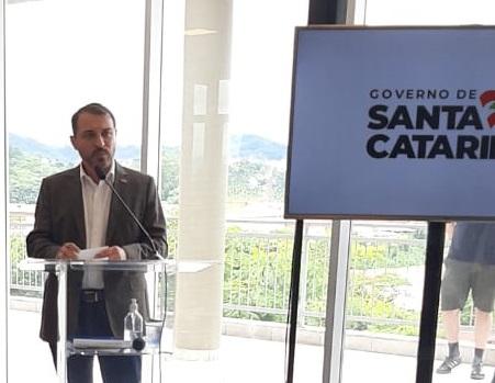 Fotografia do governador falando em um púlpito. Ao lado dele há uma tv com a bandeira do governo do estado de santa catarina.