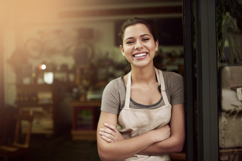 Portrait of a confident young woman standing in the doorway of a coffee shop – Foto: Getty Images/ND