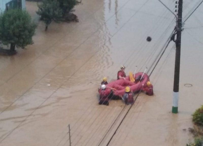Imagem de uma rua alagada e bombeiros com um bote.