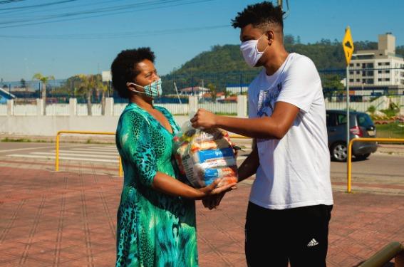 Um homem entrega uma doação de alimentos a uma mulher. Ele usa camiseta branca e ela um vestido