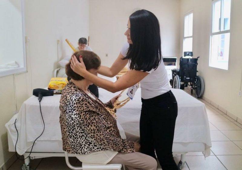 Voluntária arruma o cabelo de uma senhora no asilo