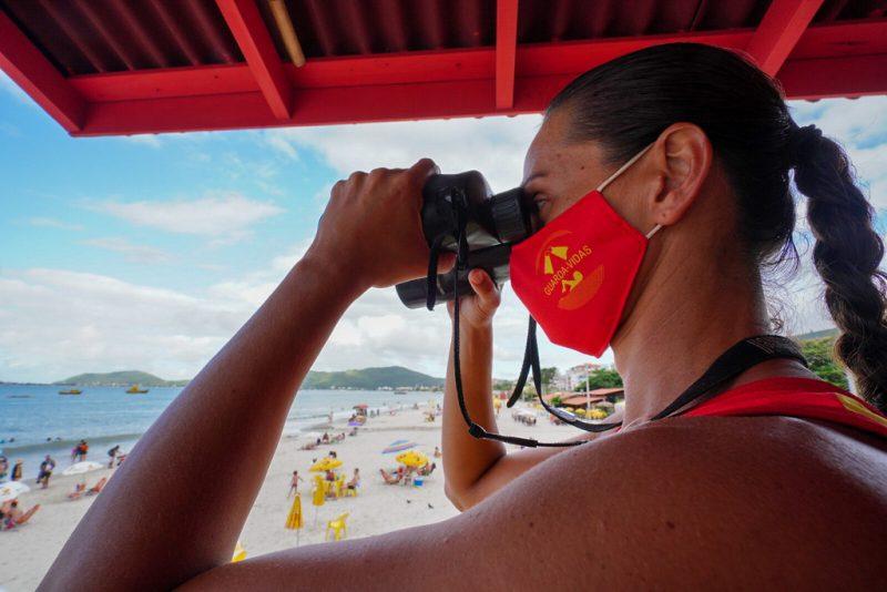 Salva vidas de máscara e observando a movimentação na praia