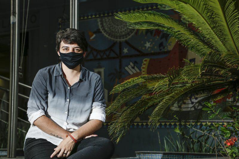 Carla Ayres, sentada e de máscara preta, com braços sobre as pernas
