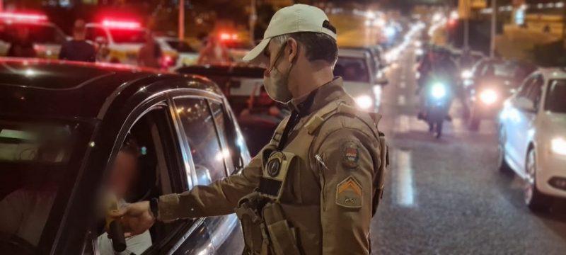 Policial faz teste de bafômetro em motorista à noite