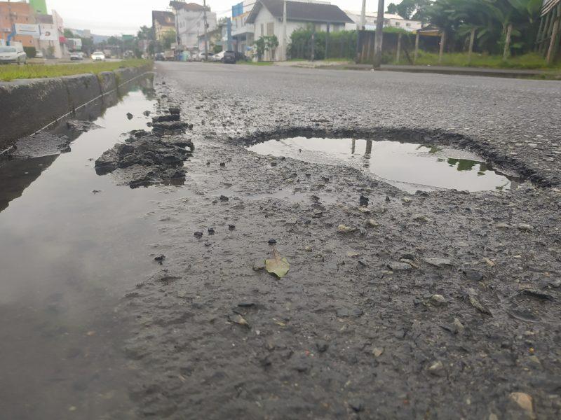 Foto de uma rua asfaltada em que aparece um buraco cheio de água no meio da pista.