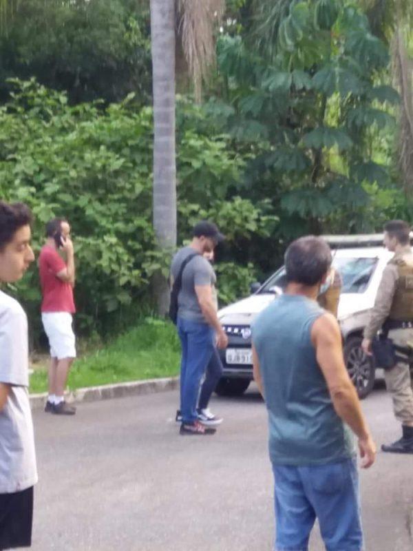 Pessoas em frente a um carro da PM perto do matagal de onde encontraram a cabeça