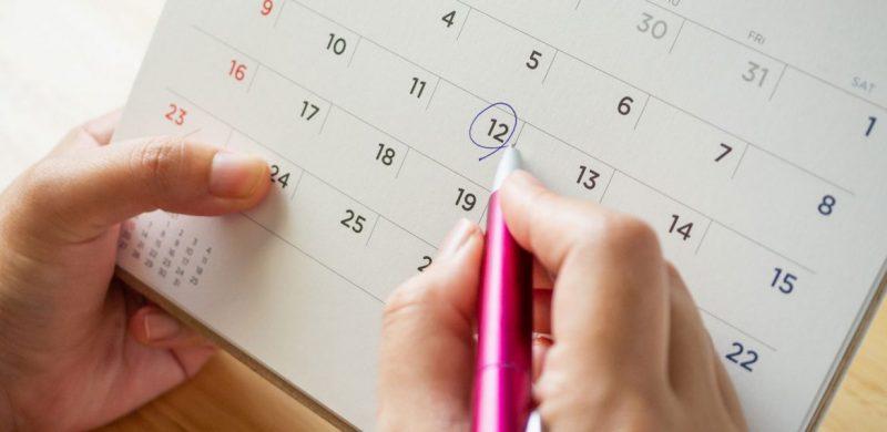 Na imagem aparece as mãos de uma pessoa segurando uma caneta rosa e um calendário. A canela circula o número 12 no calendário.