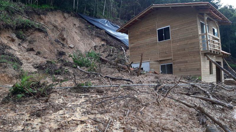 Casa destruída em Alfred Wagner. Aparece um barranco e uma casa de madeira ao lado