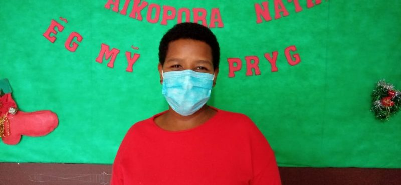 Mulher indígena negra parada em frente a um painel verde com escritas em vermelha na língua kaingang. A mulher tem o cabelo curto e usa uma camiseta vermelha e uma máscara azul. Ela está sorrindo com os olhos