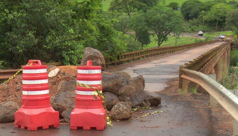 Ponte sobre o rio Chapecó fechada com pedras e terra na sua entrada e dois cones de cor laranja com listras brancos em frente e uma faixa amarelo e preto isolando o local. Do outro lado é possível ver carros parados.