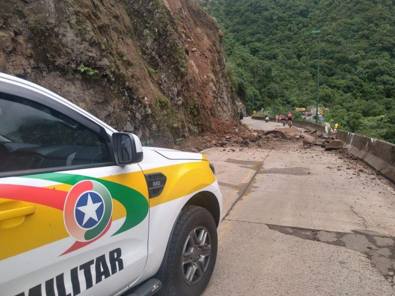 Carro da Polícia Militar branco com faixas em amarelo, verde e vermelho, com o símbolo da PM parado em frente a rodovia com rochas interditando o trânsito do local.