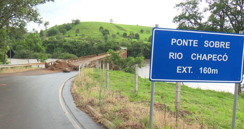 Na foto é possível ver uma parte da rodovia da integração chegando a ponte sobre o rio chapecó que está fechada com pedras e terra. Aparece também uma placa azul escrito ponte sobre o rio chapecó EXT 160 m, também aparecem árvores e um morro do outro lado da ponte