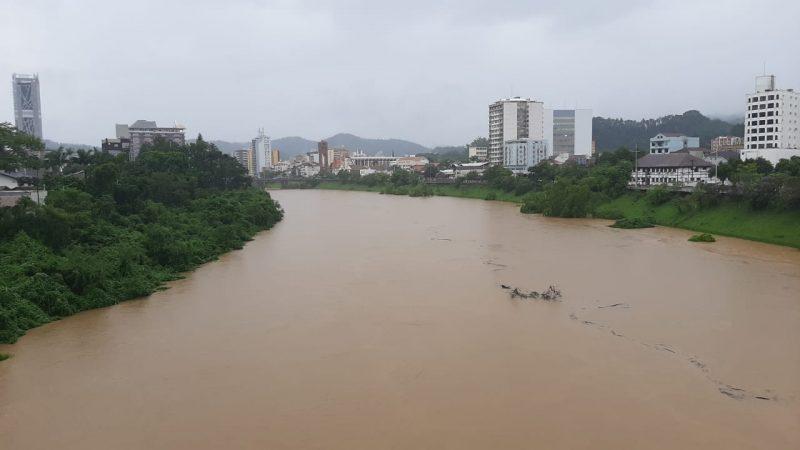 Foto do Rio Itajaí-Açu, no Centro de Blumenau. A água do está escurra, marrom, e o céu nublado. É possível observar prédios nas duas margens do rio.