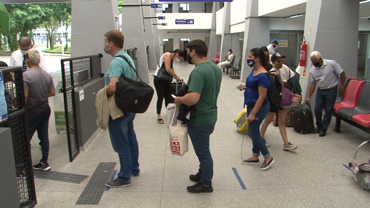 De máscara, passageiros aguardam para embarcar em ônibus. Por causa da pandemia, obra parou por duas semanas - Juliano Masselai/NDTV