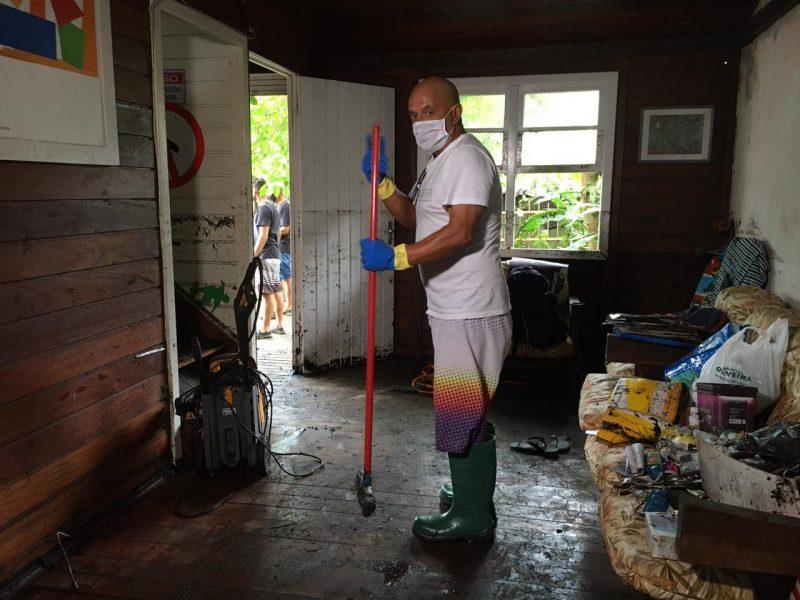 Roberto Carlos Vicente, limpando a casa alagada no desastre da Lagoa da Conceição