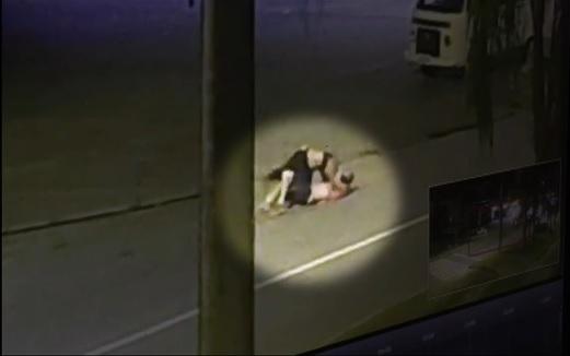Imagem de uma câmera de segurança em que aparecem duas pessoas em luta corporal no meio da rua.