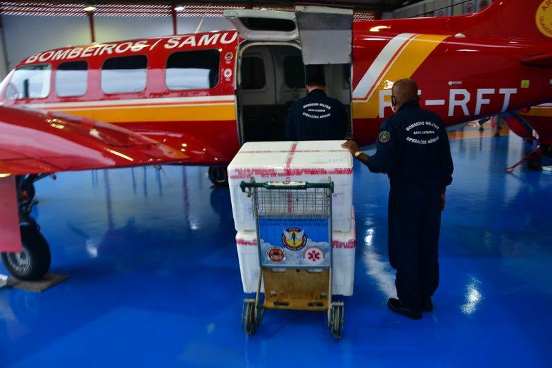 No dia seguinte, na terça-feira (19), bombeiros, policiais e profissionais da saúde se deslocaram ao Aeroporto Internacional de Florianópolis para iniciar o transporte das doses às regiões do Oeste, que as receberiam por via aérea – Foto: CBMSC/Reprodução/ND