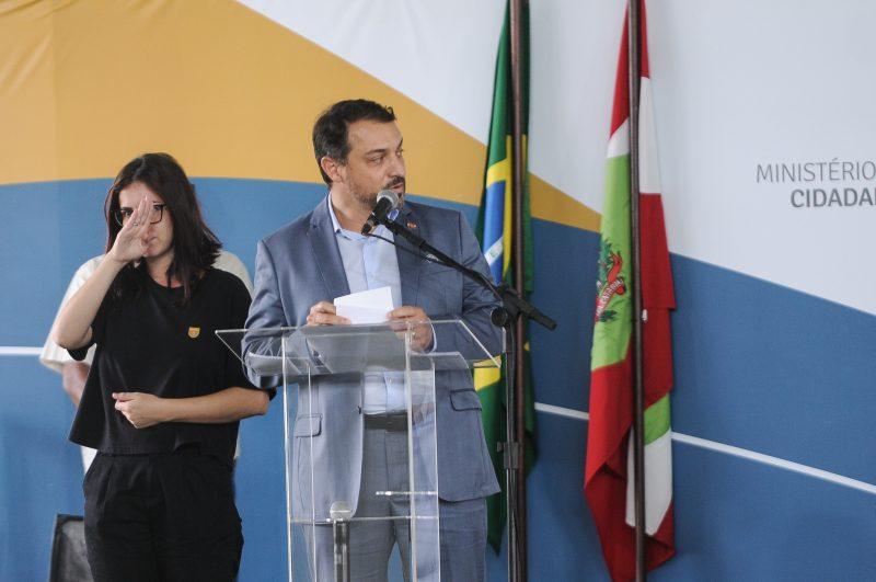 Carlos Moisés discursa, com bandeiras ao fundo e intérprete de libras ao lado