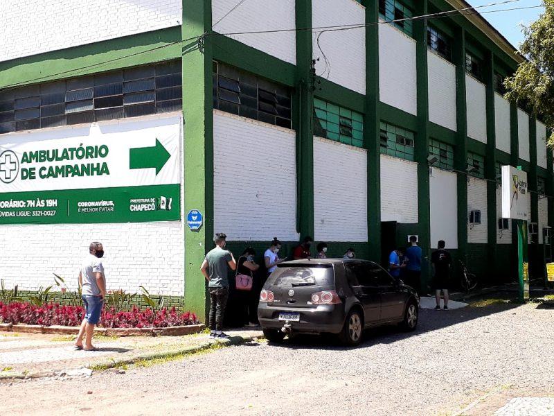 Pessoas na fila esperando para atendimento no ambulatório da Covid-19 no ginásio Ivo Silveira, em Chapecó