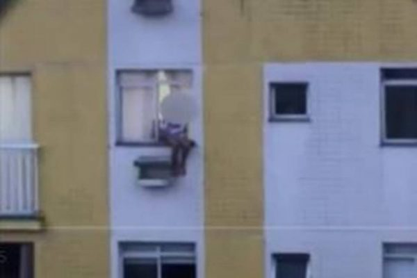 Criança aparece sentada na janela e chega a apoiar os pés na caixa do ar-condicionado – Foto: Reprodução/ND
