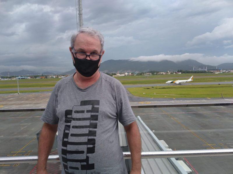 Edilson Carneiro, com o avião presidencial ao fundo, no aeroporto de Florianópolis