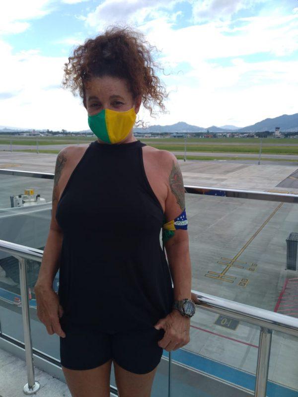Elizabeth Goulart, mulher de camisa preta e máscara verde e amarela