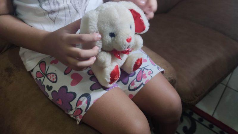 Imagem de uma menina sentada no sofá, mas não mostra o rosto dela. Aparece apenas as pernas e as mãos segurando um urso de pelúcia.
