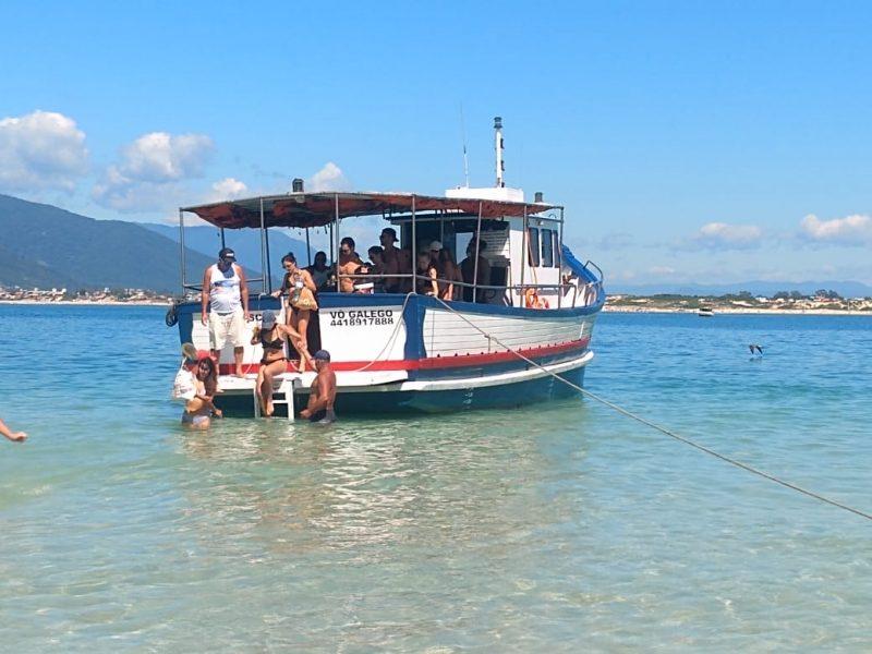Pessoas no barco descendo na água sem máscara