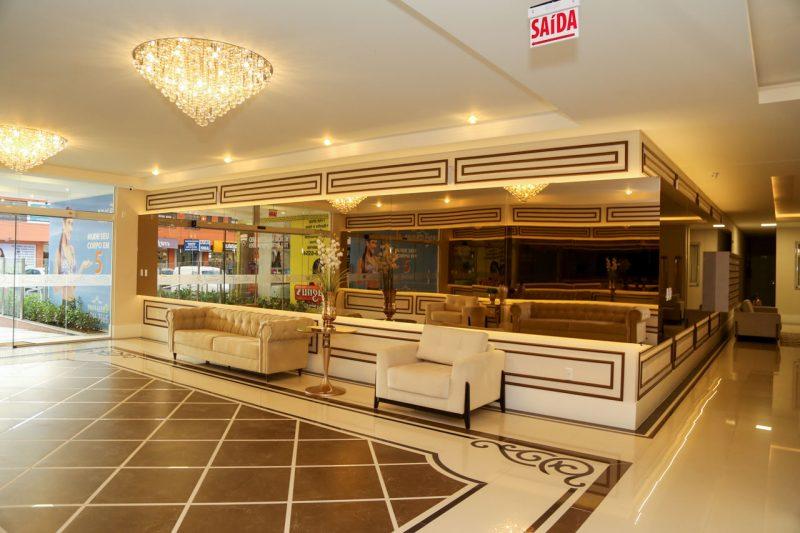 """Iluminação de destaque, grande área espelhada e piso com padrão diferenciado chamam atenção no hall do <a href=""""http://www.amconstrucoes.com.br/empreendimentos/dolce-vitta/"""" target=""""_blank"""" rel=""""noopener noreferrer"""">condomínio Dolce Vitta</a>, em Palhoça &#8211; Foto: AM Construções/Divulgação"""
