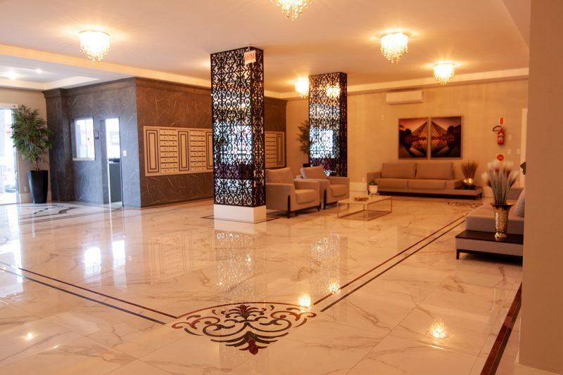 """Hall do <a href=""""http://amconstrucoes.com.br/empreendimentos/lidia-dircksen-residence/"""" target=""""_blank"""" rel=""""noopener noreferrer"""">condomínio Lídia Dircksen</a>, em São José: ampla área de circulação e decoração clássica &#8211; Foto: AM Construções/Divulgação"""