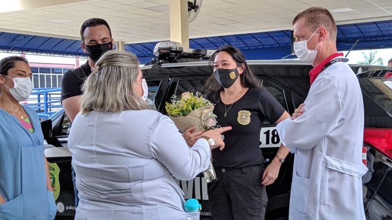 Técnica de enfermagem recebe as flores das mãos da delegada regional Tânia Harada – Foto: Juan Todescatt