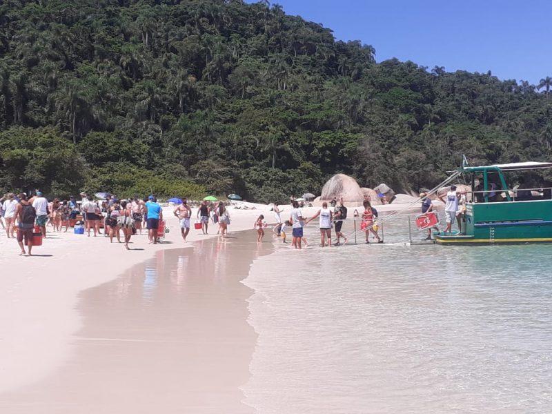Pessoas descendo de embarcação na praia