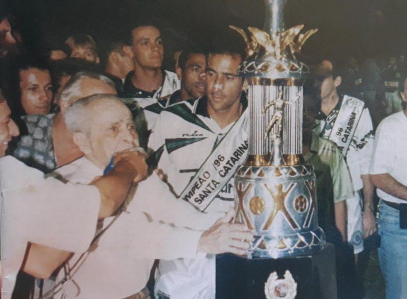 Em 1996, o Figueirense conquistou a o título da Copa Santa Catarina. Por ironia do destino, o troféu levou o nome de um dos maiores ídolos da história do rival Avaí, o ex-atacante Saul Oliveira, que aparece na foto entregando o troféu para o capitão do alvinegro, Vinívius Eutrópio, hoje treinador do Joinville, e campeão da mesma Copa SC na semana passada. No canto direito, aparece o saudoso repórter Evaldo Filho – Foto: Memorial Alvinegro/ND