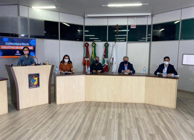 Coletiva de imprensa realizada para atualização das medidas de combate à Covid-19 em Xanxerê, Na imagem aparece cinco pessoas sentadas em um auditório. Entre eles está o prefeito de Xanxerê Oscar Martarello e demais autoridades da saúde e de segurança do município.