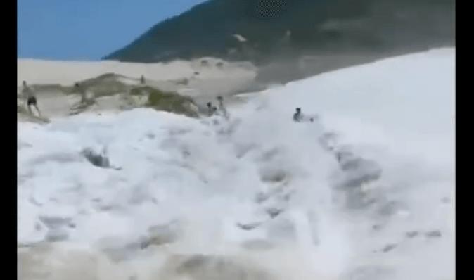 Vídeo flagra momento em que onda invade areia e atinge família na Praia do Santinho