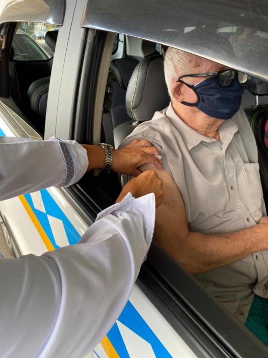 idoso sendo vacinado em sistema drive thru